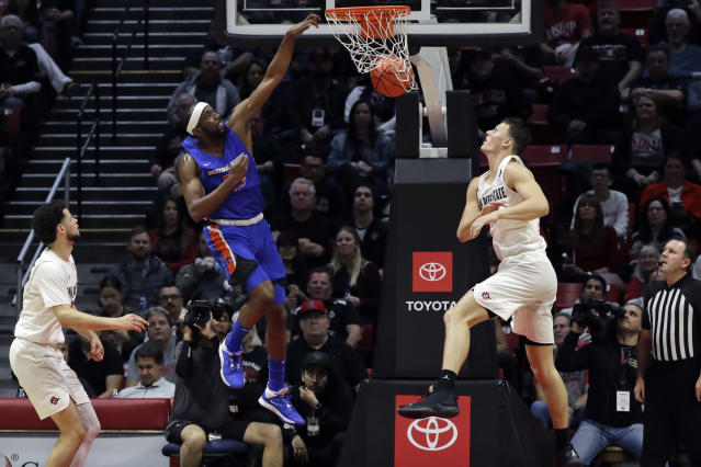 Boise State forward RJ Williams dunks as San Diego State forward Yanni Wetzell, right, and guard Jordan Schakel, left, watch during the first half of an NCAA college basketball game Saturday, Jan. 11, 2020, in San Diego. (AP Photo/Gregory Bull)