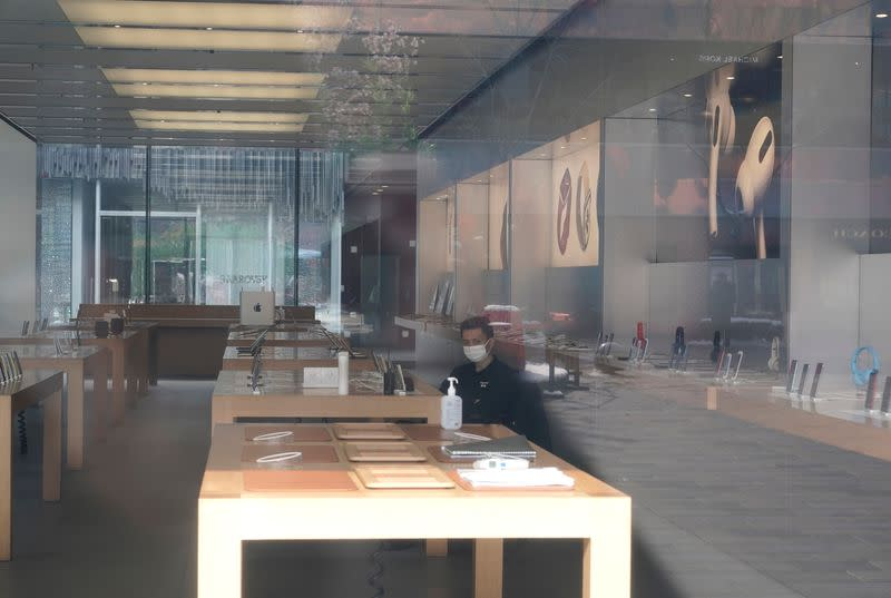 Security personnel wearing a face mask is seen in a closed Apple store at Sanlitun in Beijing