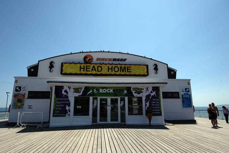 """A Bournemouth, Christchurch and Poole (BCP) Council message is displayed on a screen telling people to 'Save lives', 'Think Twice' and 'Head home if beach is too busy"""" at Bournemouth pier, Dorset."""