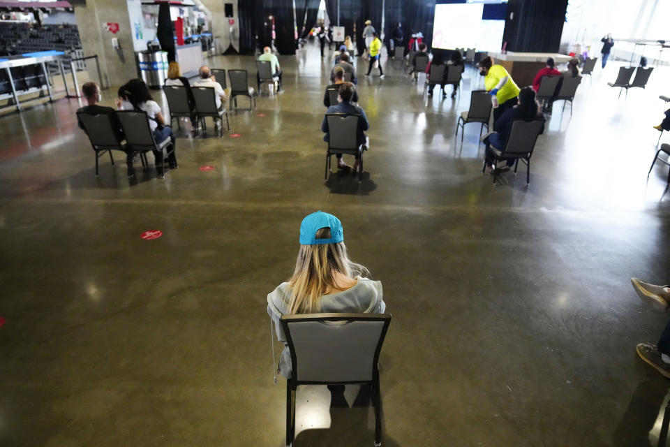 FILE - In this March 25, 2021, file photo, people wait to receive a vaccine at Mercedes-Benz Stadium in Atlanta. A new poll from The Associated Press-NORC Center for Public Affairs Research shows that the percentage of Americans resisting getting inoculated has shrunk in the past few months. But it's still not enough to pull America out of the pandemic, and reach herd immunity. (AP Photo/Brynn Anderson, File)