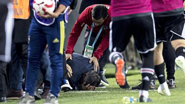 Besiktas manager Senol Gunes fell to the ground after being struck in the head by an object thrown from the stands. (AAP)