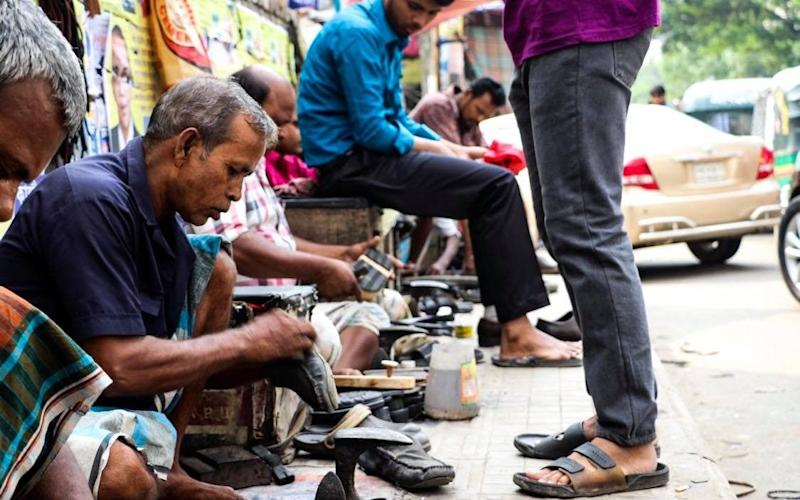 In emerging economies like Bangladesh, white-collar workers who once wore suits to work and stopped off to have their shoes shined are now forced to take up this low-paid job themselves - Susannah Savage