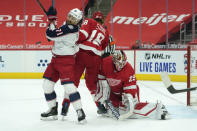 Columbus Blue Jackets left wing Nick Foligno (71) tries to redirect the puck as Detroit Red Wings defenseman Marc Staal (18) defends in front of goaltender Thomas Greiss (29) in the first period of an NHL hockey game Monday, Jan. 18, 2021, in Detroit. (AP Photo/Paul Sancya)
