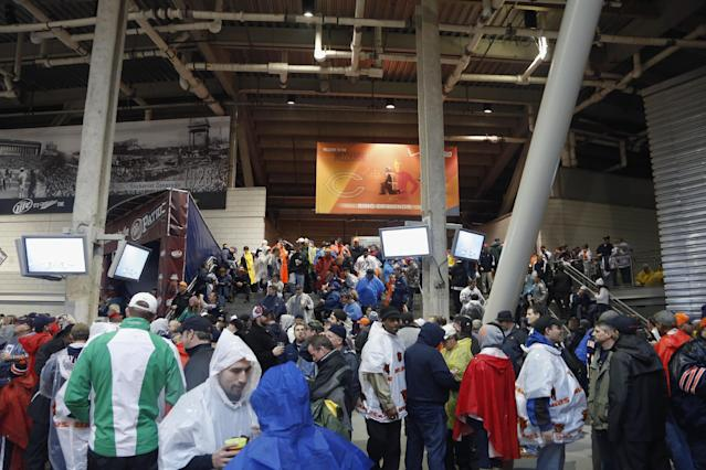 Fans seek shelter in the concourse area at Soldier Field as a severe storm blows through the area during the first half of an NFL football game between the Chicago Bears and Baltimore Ravens, Sunday, Nov. 17, 2013, in Chicago. Play was suspended in the game. (AP Photo/Charles Rex Arbogast)