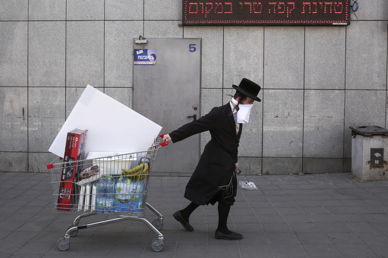 An ultra-Orthodox Jew wears an improvised protective face mask as he pulls a supermarket cart on a mainly deserted street because of the government's measures to help stop the spread of the coronavirus, in Bnei Brak, a suburb of Tel Aviv, Israel, Friday, April 3, 2020.   The military plans to send troops in to assist local authorities with coronavirus control.   (AP Photo/Oded Balilty)