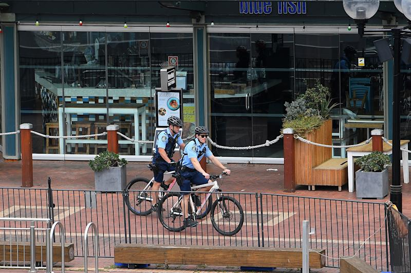 Police patrol closed businesses around the usually busy Darling Harbour precinct in Sydney on Thursday. Source: AAP