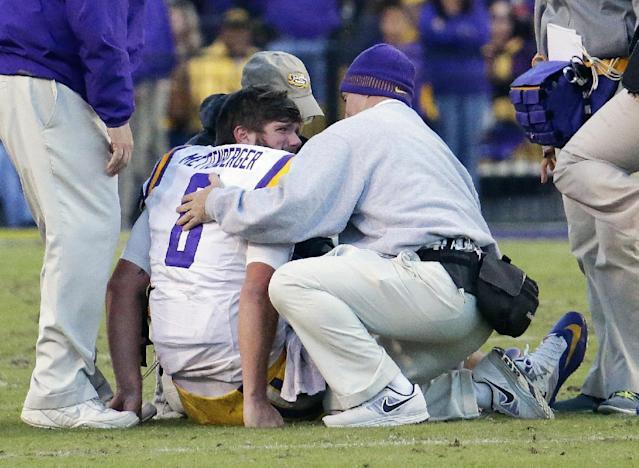 LSU quarterback Zach Mettenberger (8) gets help from trainers after he was injured in the fourth quarter against Arkansas in an NCAA college football game in Baton Rouge, La., Friday, Nov. 29, 2013. LSU defeated Arkansas 31-27. (AP Photo/Bill Haber)