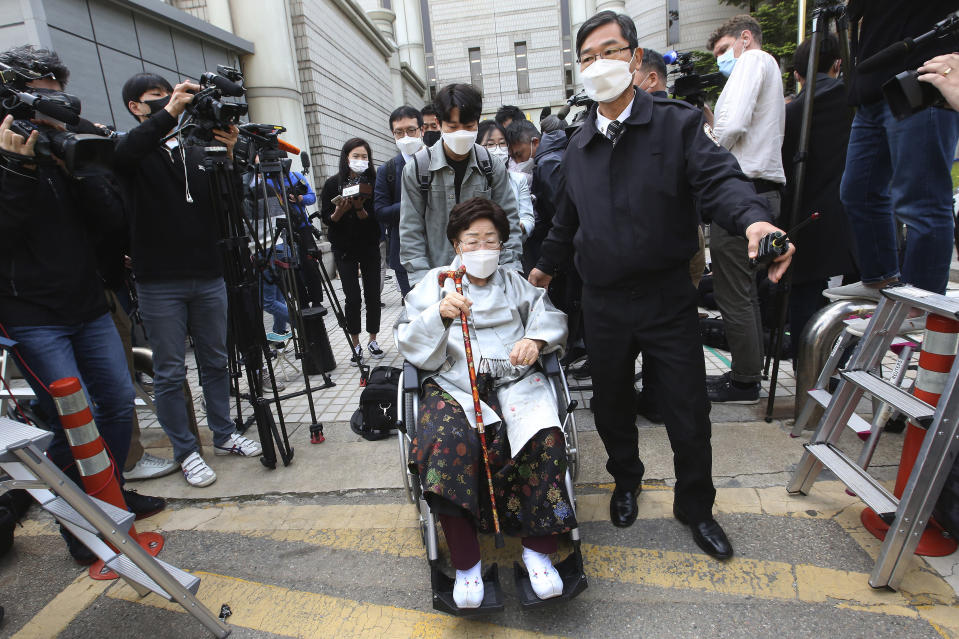 Former South Korean comfort woman Lee Yong-soo in a wheelchair leaves the Seoul Central District Court in Seoul, South Korea, Wednesday, April 21, 2021. A South Korean court on Wednesday rejected a claim by South Korean sexual slavery victims and their relatives who sought compensation from the Japanese government over their wartime sufferings. (AP Photo/Ahn Young-joon)