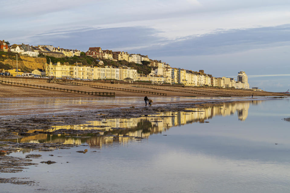 A view of the seafront of West Marina in St Leonards-on-Sea, East Sussex, taken from the beach at low tide. The buildings are reflected in the calm sea and sand and the setting sun has made the building glow.