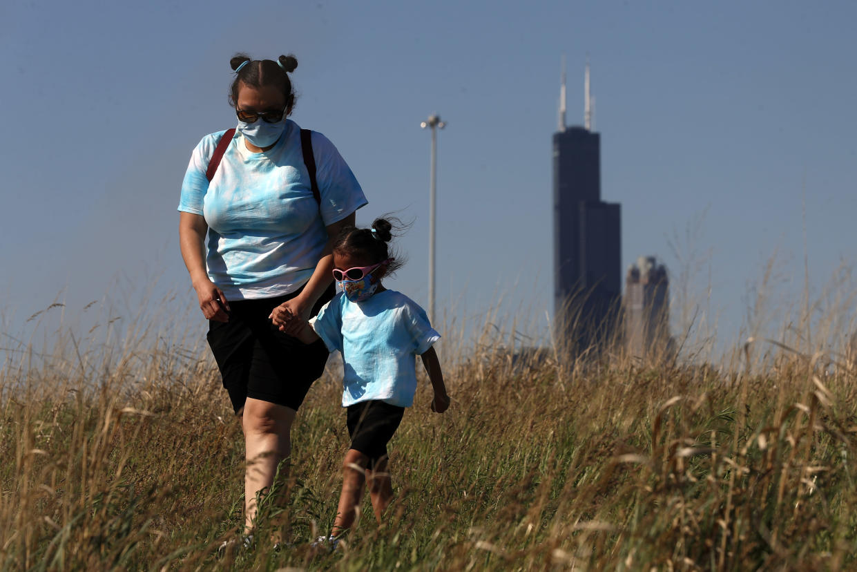 A mother walks with her daughter wearing face masks in Chicago's Henry C. Palmisano Nature Park, Friday, June 4, 2021. (Shafkat Anowar/AP)