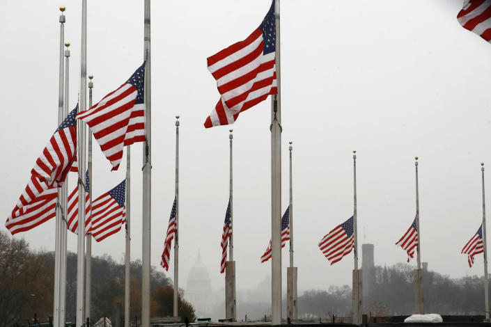 With a misty U.S. Capitol in the distance, the American flags surrounding the Washington Monument fly at half-staff on Dec. 1 in Washington, after President Trump directed that flags be flown at half-staff for 30 days to honor the memory of former President George H.W. Bush. (Photo: Jacquelyn Martin/AP)
