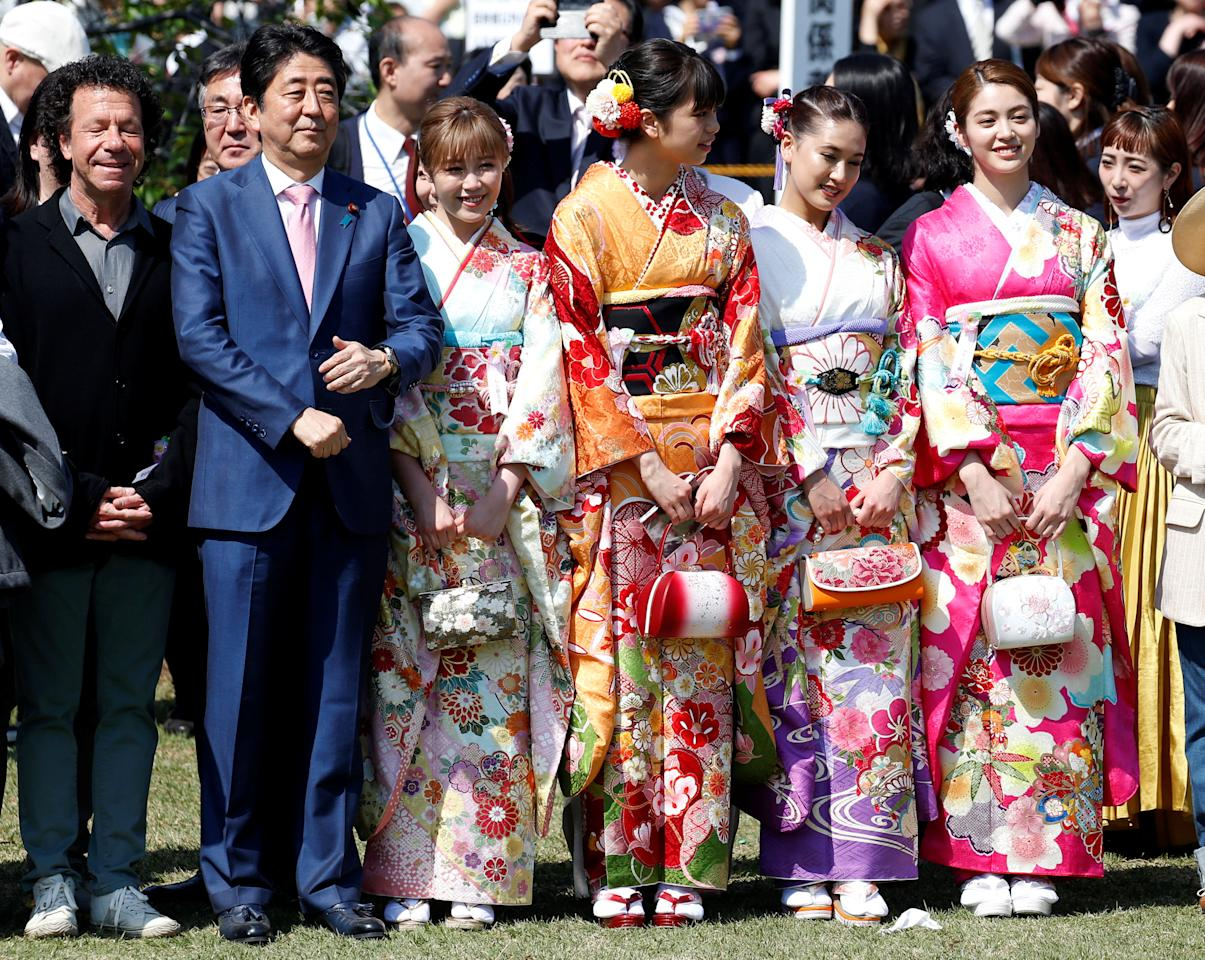Japan's Prime Minister Shinzo Abe poses with members of pop group E-girls in kimonos during a cherry blossom viewing party at Shinjuku Gyoen park in Tokyo, Japan, April 21, 2018.  REUTERS/Toru Hanai