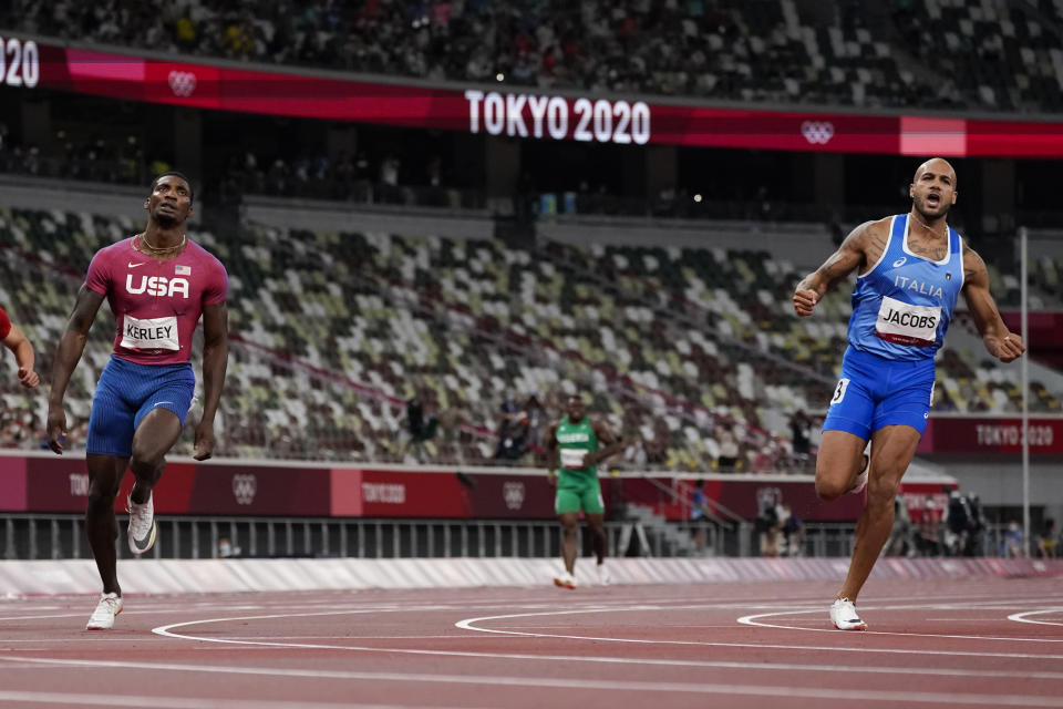 Lamont Jacobs, right, of Italy, celebrates after winning the men's the 100-meter final at the 2020 Summer Olympics, Sunday, Aug. 1, 2021, in Tokyo.(AP Photo/Petr David Josek)