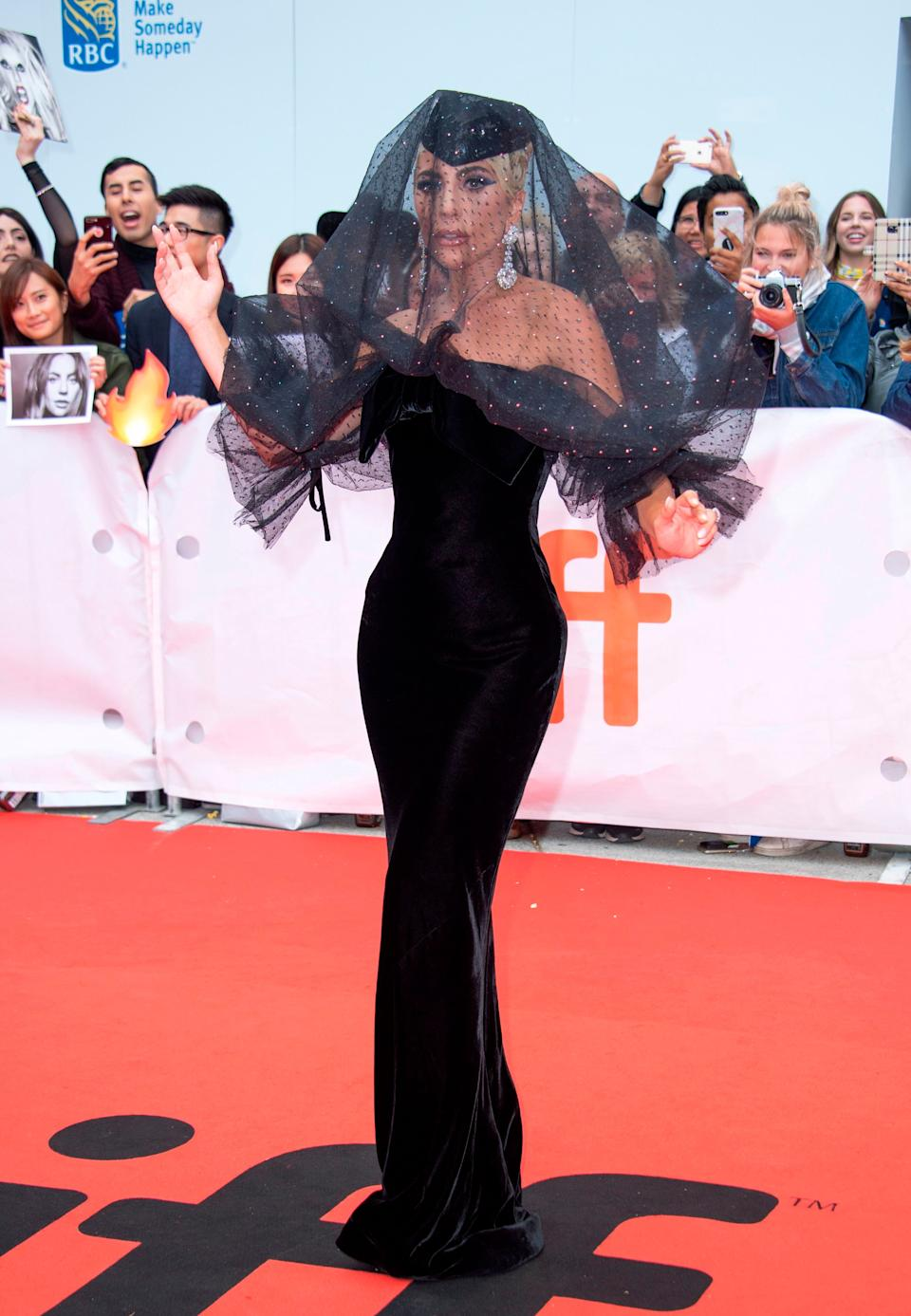 """The """"Paparazzi"""" singer goes for full Old Hollywood drama in this black gown and veil by Armani Privé at the Toronto International Film Festival in September 2018."""