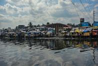 TOPSHOT - This photo taken on March 18, 2020 shows a general view of a slum area along the river in Manila. - Asian nations have imposed increasingly heavy measures to fight the outbreak of the COVID-19 coronavirus, the Philippines has ordered half its population of some 110 million to stay home. (Photo by Maria TAN / AFP) / TO GO WITH Health-virus-Philippines-poverty,FOCUS by Joshua Melvin and Ron Lopez (Photo by MARIA TAN/AFP via Getty Images)