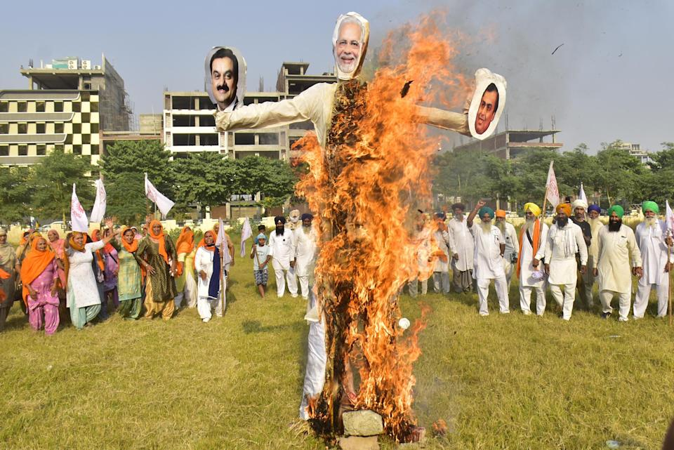 People raise slogans while burning an effigy of Prime Minister Narendra Modi, Chairman of Reliance Industries, Mukesh Ambani and Chairman of the Adani Group Gautam Adani, in protest against corporate businesses under the banner of Kisan Mazdoor Sangharsh Committee, at Ranjeet Avenue Ground, on October 23, 2020 in Amritsar. (Photo: Hindustan Times via Getty Images)