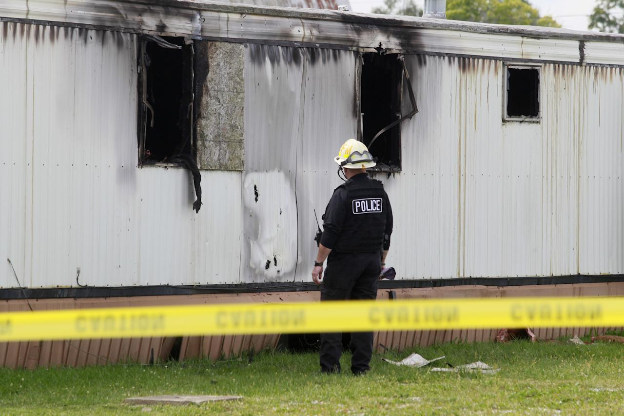 Wm. Timothy Spradlin, with the Division of the State Fire Marshal, investigates into the scene of a fire that killed five children and one adult on Sunday, Sept. 15, 2013, in Tiffin, Ohio. The fire was reported shortly before 8 a.m. Sunday in a mobile home park in Tiffin, about 50 miles southeast of Toledo, Ohio. (AP Photo/The Blade, Amy Voigt)