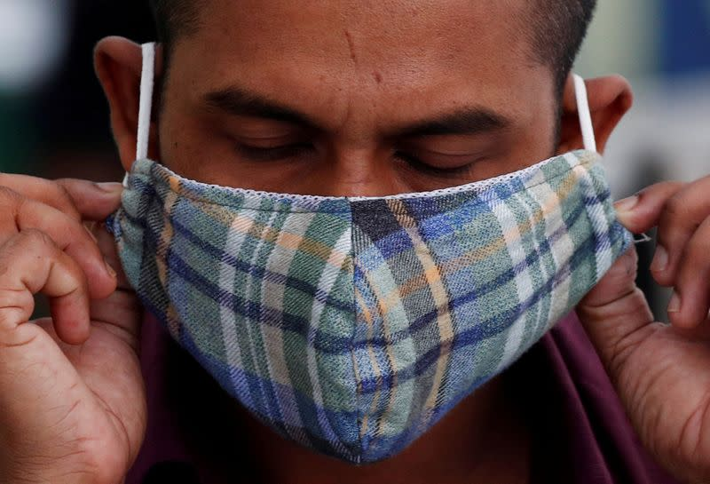 FILE PHOTO: A migrant worker puts on a mask at a dormitory, amid the coronavirus disease (COVID-19) outbreak in Singapore
