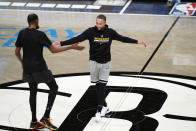 Golden State Warriors guard Stephen Curry, right, and Brooklyn Nets forward Kevin Durant, former teammates, greet each other at center court before an NBA basketball game Tuesday, Dec. 22, 2020, in New York. (AP Photo/Kathy Willens)