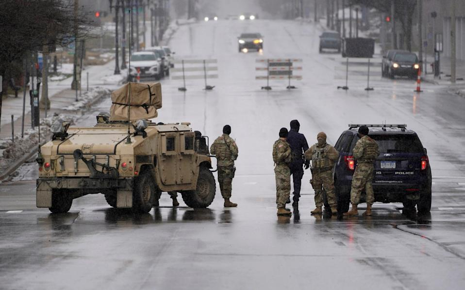 Michigan National Guard and Lansing Police officers patrol at a closed street outside the state capitol in Lansing - AP