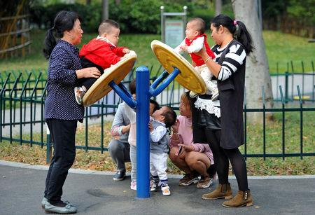 Women play with children at a park in Jinhua, Zhejiang province