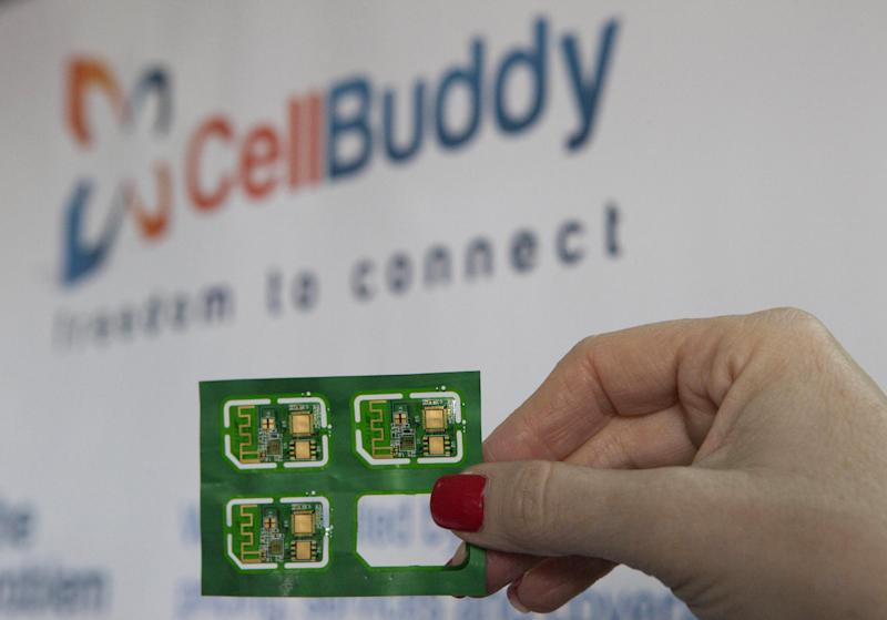 In this photograph made on Thursday Nov. 28, 2013 an employee holds a CellBuddy sim cards at the company's office in Tel Aviv, Israel. For international travelers tired of paying steep roaming charges on their cellphones, an Israeli start-up says it has found a solution. Cell Buddy says its app can turn any smartphone into a local handset, allowing travelers to choose from an array of calling and data plans with carriers in dozens of countries. (AP Photo/Dan Balilty)