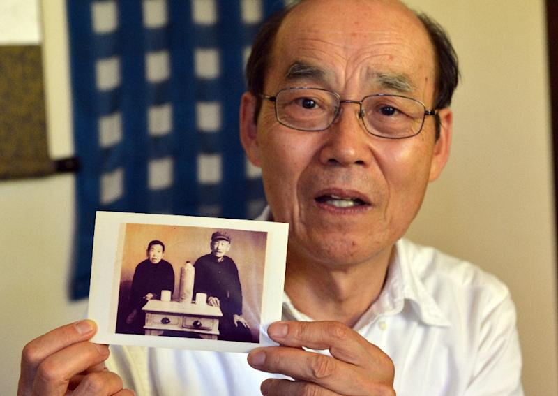Yohachi Nakajima, 73, holds a picture of his Chinese adopted parents, at his home in Tokyo (AFP Photo/Yoshikazu Tsuno)