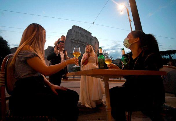 PHOTO: People gather for an aperitif drink outside a bar by the Colosseum in Rome, Italy, on May 18, 2020, as the nationwide lockdown is eased after over two months of measures aimed at curbing the spread of the novel coronavirus. (Filippo Monteforte/AFP via Getty Images)