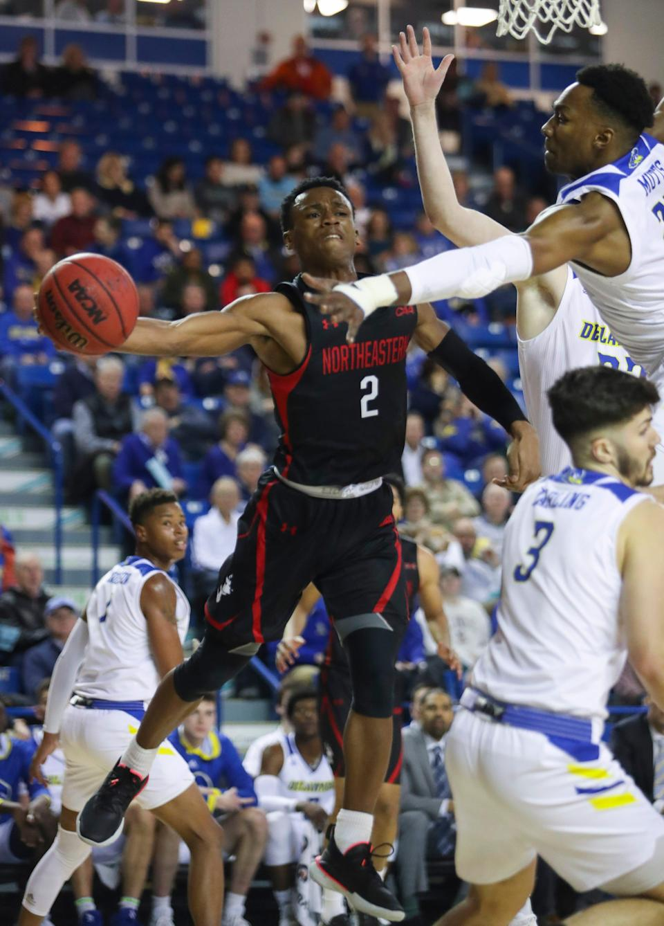 Northeastern's Tyson Walker (2) throws a pass around Delaware's Justyn Mutts (top right) in the first half at the Bob Carpenter Center Thursday.