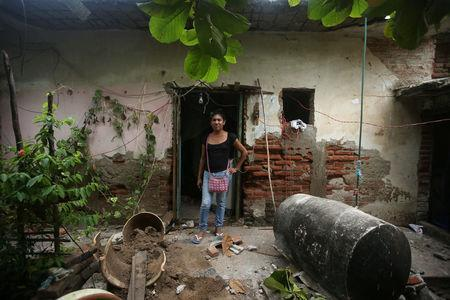 Peregrina, 26, an indigenous Zapotec transgender woman also know as Muxe, poses for a photo outside of her house destroyed after an earthquake that struck on the southern coast of Mexico late on Thursday, in Juchitan, Mexico, September 10, 2017. REUTERS/Edgard Garrido