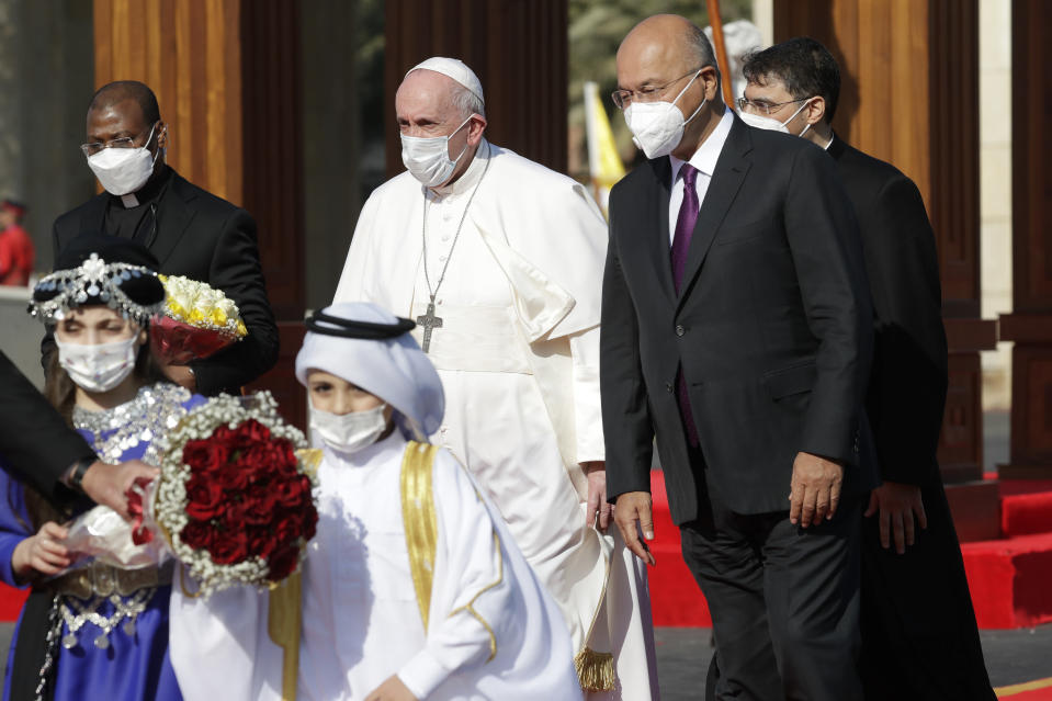 Pope Francis is welcomed by Iraqi President Barham Salih, at Baghdad's Presidential Palace, Iraq, Friday, March 5, 2021. Pope Francis has arrived in Iraq to urge the country's dwindling number of Christians to stay put and help rebuild the country after years of war and persecution, brushing aside the coronavirus pandemic and security concerns. (AP Photo/Andrew Medichini)