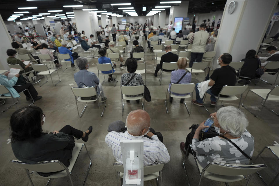 FILE - In this June 6, 2021, file photo, local residents wait for receiving the Moderna coronavirus vaccine at a mass vaccination center in Yokohama, near Tokyo. After months of delays due to political and bureaucratic bungling as well as a shortage of vaccines, inoculations in Japan are taking off, and the drive is now racing down to the wire with the Olympics starting in one month. (AP Photo/Eugene Hoshiko, File)