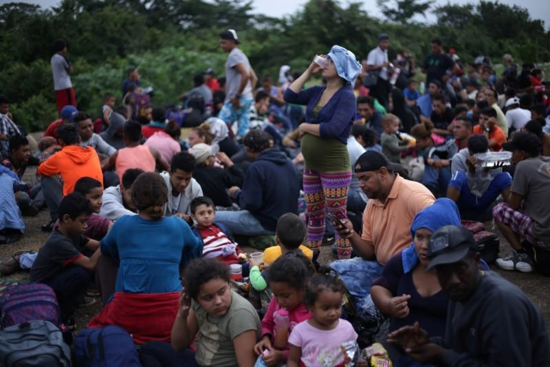 Migrants from Central America, part of a caravan travelling to the U.S., wait to cross into Mexico at the border between Guatemala and Mexico, in El Ceibo
