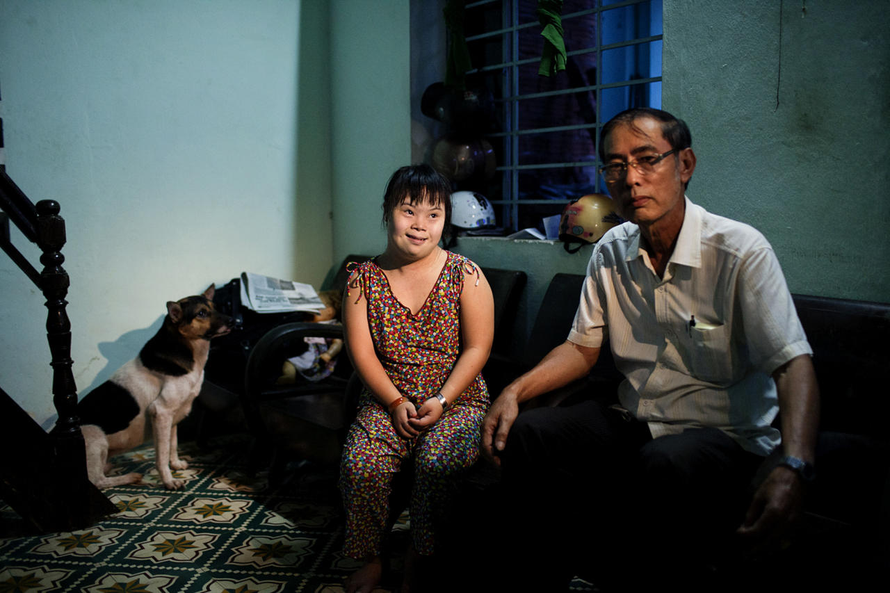 In this photo taken Aug. 7, 2012, Vo Thi Thuy Nga, 24, left, and her uncle Vo Duoc sit inside their home in Danang, Vietnam. She was born with physical and mental disabilities that a rehabilitation center's director said were caused by their parents' exposure to the chemical dioxin in the defoliant Agent Orange. Washington was slow to respond, but on Thursday, Aug. 9, 2012 the U.S. for the first time will begin cleaning up leftover dioxin that was stored at the former military base, now part of Danang's airport. (AP Photo/Maika Elan)