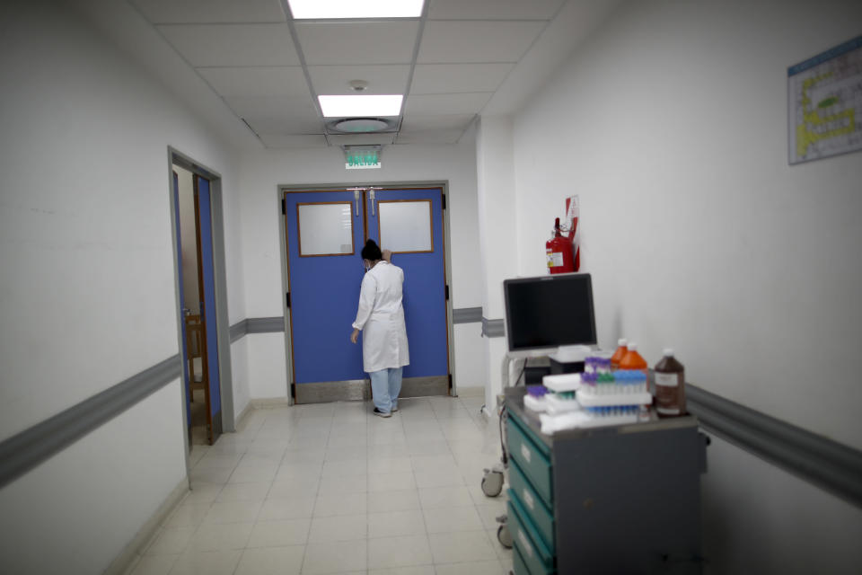 Dr. Veronica Verdino approaches the door to tell the son of a COVID-19 patient that his father died at Llavallol Dr. Norberto Raúl Piacentini Hospital in Lomas de Zamora, Argentina, Saturday, May 8, 2021. General ward medics like Verdino have learned to master intubations, complex sedation drugs, electrocardiograms, CT scans and laryngoscopes as oxygen supplies become scarce. (AP Photo/Natacha Pisarenko)