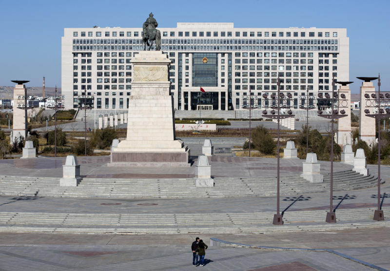 In this photo taken on Wednesday, Oct. 24, 2012, a couple visits a public square against the government office building in Xilinhot in northern China's Inner Mongolia. Buying and selling office is so rampant in China that it has eroded public trust in officialdom, undermining the ruling Communist Party's image as an institute that promotes the competent, not the connected. Even though Chinese leaders have vowed to eradicate the practice, it has showed no sign of abatement. (AP Photo/Andy Wong)