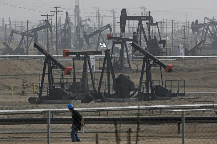 FILE - In this Jan. 16, 2015, file photo, a person walks past pump jacks operating at the Kern River Oil Field in Bakersfield, Calif. California's oil rich Kern County is voting on a revised plan that could permit tens of thousands of oil and gas wells in the next two decades. The plan had to be rewritten after environmental groups sued and a state appeals court found the county's permit system could threaten the region's air and water. (AP Photo/Jae C. Hong, File)
