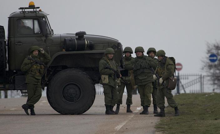 Unidentified gunmen wearing camouflage uniforms block the road toward the military airport at the Black Sea port of Sevastopol in Crimea, Ukraine, Friday, Feb. 28, 2014. Heightened security is evident with Russian military around Sevastopol, the location for Russia military bases, military airport and Naval Base, while unidentified armed men wearing uniforms without insignia were patrolling another airport serving the regional capital, Ukraine's new Interior Minister Arsen Avakov said on Friday. (AP Photo/Ivan Sekretarev)