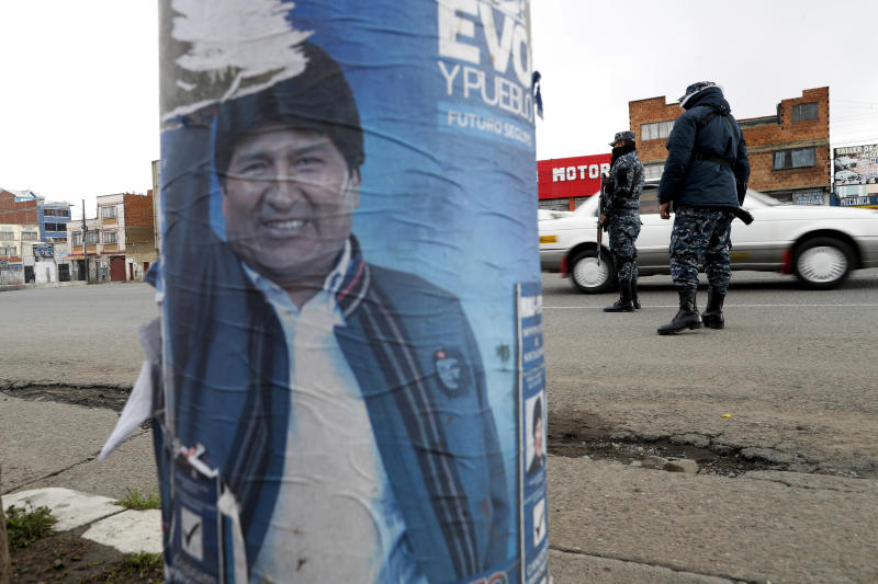 A torn electoral poster of former President Evo Morales covers a street lamp post as soldiers control traffic in El Alto, on the outskirts of La Paz, Bolivia, Tuesday, Nov. 12, 2019. Bolivia faced political vacuum Tuesday, while Morales fled the country on a Mexican plane following weeks of protests fed by allegations of electoral fraud in the Oct. 20 presidential election that he claimed to have won. (AP Photo/Natacha Pisarenko)