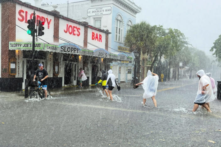 Determined visitors head for Sloppy Joe's Bar while crossing a flooded Duval Street as heavy winds and rain pass over Key West, Fla., on July 6, 2021. (Rob O'Neal / AP)