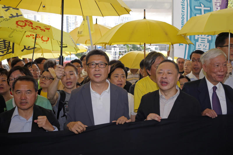 Occupy Central leaders, from left, Lee Wing-tat, Chan Kin-man, Benny Tai and Chu Yiu-ming enter a court in Hong Kong, Wednesday, April 24, 2019. The court is preparing to sentence nine leaders of massive 2014 pro-democracy protests convicted last month of public nuisance offenses. The sentences to be handed down Wednesday are seen as an effort by the government of the semi-autonomous Chinese territory to draw a line under the protests. (AP Photo/Kin Cheung)