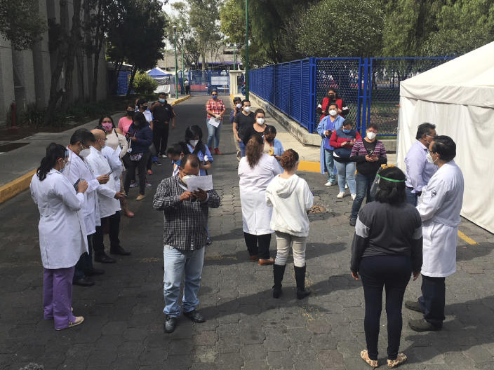 Juarez public hospital health workers wait on a street after a 7.5 earthquake sent them out from their work areas, in Mexico City, Tuesday, June 23, 2020. The earthquake centered near the resort of Huatulco in southern Mexico swayed buildings Tuesday in Mexico City and sent thousands into the streets. (AP Photo/Eduardo Verdugo)