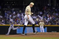 Arizona Diamondbacks relief pitcher Joe Mantiply pauses on the mound with a new baseball after giving up a home run to Los Angeles Dodgers' Steven Souza, left, as Diamondbacks shortstop Nick Ahmed, right, waits for the next batter during the eighth inning of a baseball game Friday, June 18, 2021, in Phoenix. (AP Photo/Ross D. Franklin)