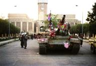 FILE - In this Sept. 28, 1996 file photo, tanks manned by Taliban fighters and decorated with flowers are seen in front of the the damaged Presidential palace in Kabul, Afghanistan. The Taliban fighters who rolled into Afghanistan's capital and other cities in recent days appear awestruck by the towering apartment blocks, modern office buildings and shopping malls. When the Taliban last seized power, in 1996, the country had been ravaged by civil war and the capital was in ruins. (AP Photo/ B.K.Bangash, File)