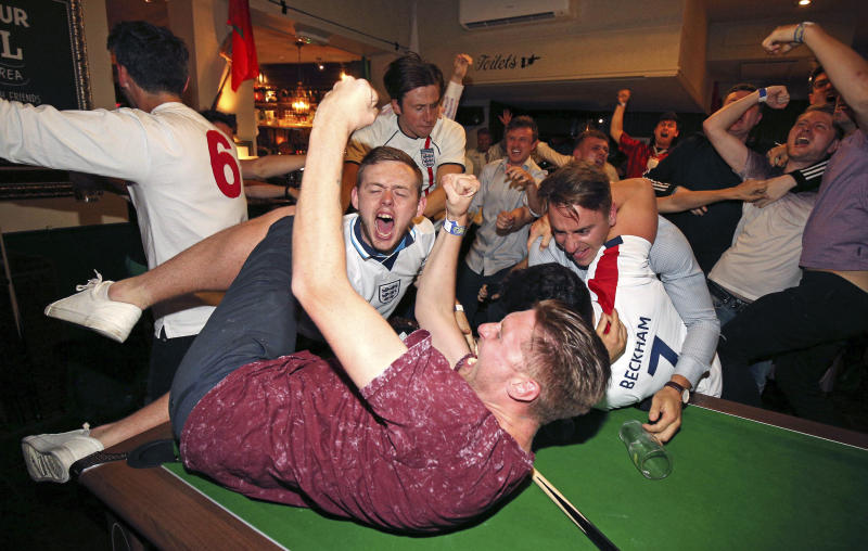 England supporters celebrate Harry Kane's winning goal as fans watch the World Cup soccer match between Tunisia and England at the Lord Raglan Pub in London, Monday, June 18, 2018. (Nigel French/PA via AP)