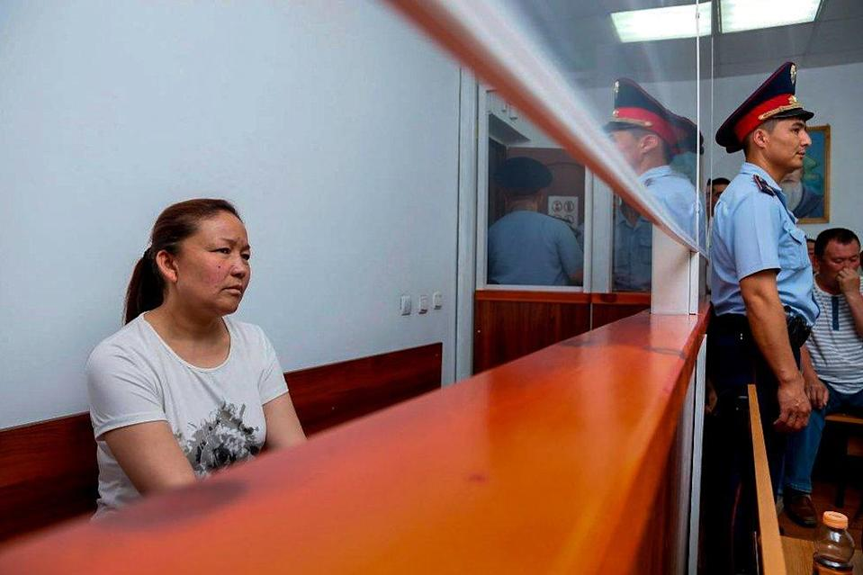 A picture taken on July 13, 2018 shows Sayragul Sauytbay, 41, an ethnic Kazakh Chinese national and former employee of the Chinese state, who is accused of illegally crossing the border between the countries to join her family in Kazakhstan, sits inside a defendants' cage during a hearing at a court in the city of Zharkent.