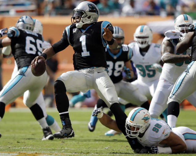 Carolina Panthers quarterback Cam Newton (1) escapes a sack by Miami Dolphins defensive tackle Jared Odrick (98) during the first half of an NFL football game on Sunday, Nov. 24, 2013, in Miami Gardens, Fla. (AP Photo/Lynne Sladky)