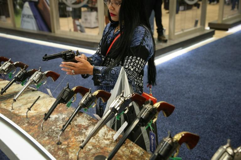 A woman inspects a firearm at the NRA convention