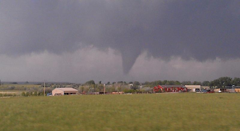 A Thursday, June 7, 2012 photo provided by Andrew Kniss shows a funnel cloud, seen from Kniss's car on Highway 34, near Wheatland, Wyoming. The rare quarter-mile-wide tornado cut a swath across mainly open country in southeastern Wyoming, damaging homes, derailing empty train cars and leaving one person with minor injuries, officials said. The twister was part of a powerful storm system that rolled through parts of Colorado and Wyoming Thursday afternoon and evening, packing heavy rains, high winds and hail. (AP Photo/Andrew Kniss)
