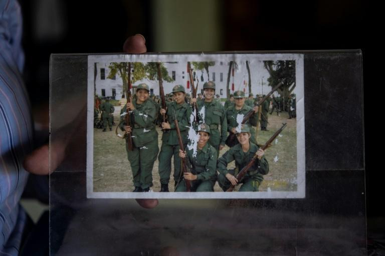 Ismaira Figueroa, a sniper for the Bolivarian militia, shows a picture of her (2R top) posing with comrades after their graduation, during an interview with AFP at her house in Baruta neighbourhood in Caracas